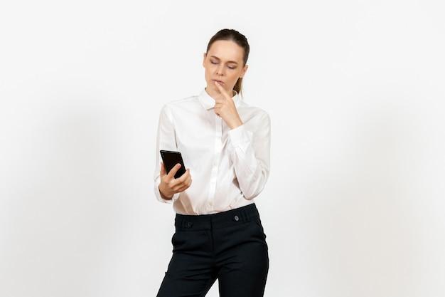 Female worker in elegant white blouse using phone on white
