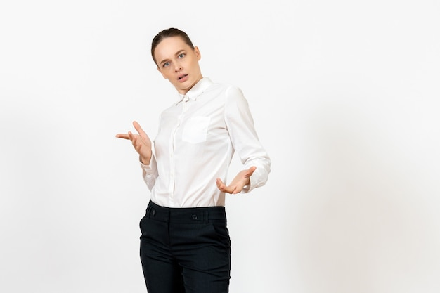 Female worker in elegant white blouse with confused face on white