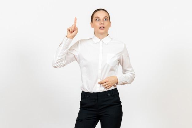 Lavoratrice in elegante camicetta bianca con la faccia pensante su bianco