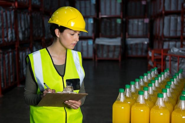 Lavoratore di sesso femminile che esamina le bottiglie di succo in fabbrica