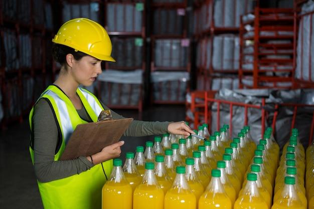 Lavoratore di sesso femminile che esamina le bottiglie di succo