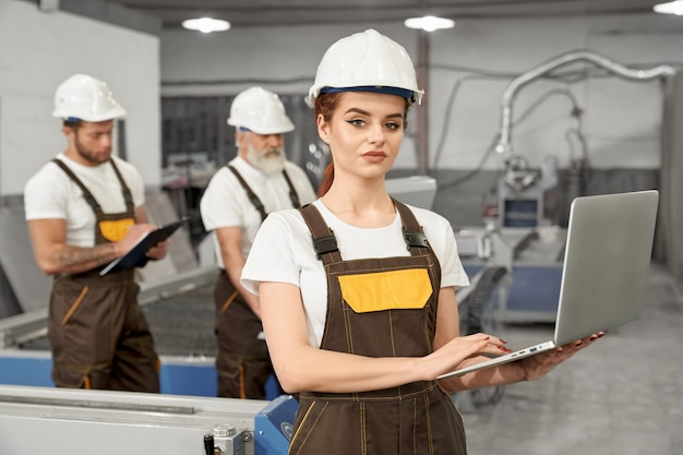 Female worker of factory posing with notebook.