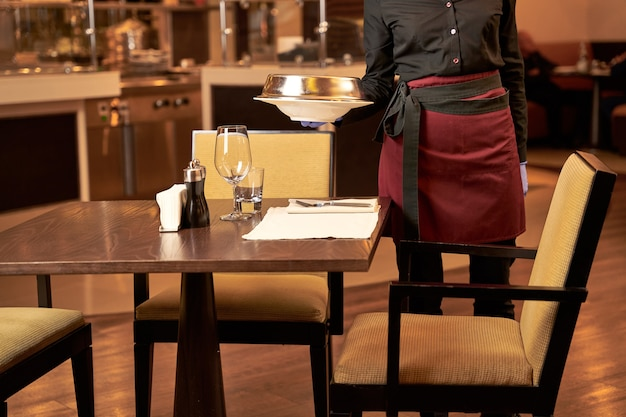 Female worker of a famous restaurant coming with a meal to an empty table and putting it next to glasses