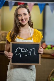 Работница держит доску с открытым знаком