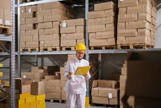 창 고에 서있는 동안 서류와 함께 폴더를 들고 여성 노동자. 선반 위의 모든 상자. 보호 복, 헬멧 헬멧.