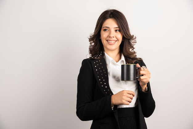 Lavoratrice che tiene il tè con l'espressione felice