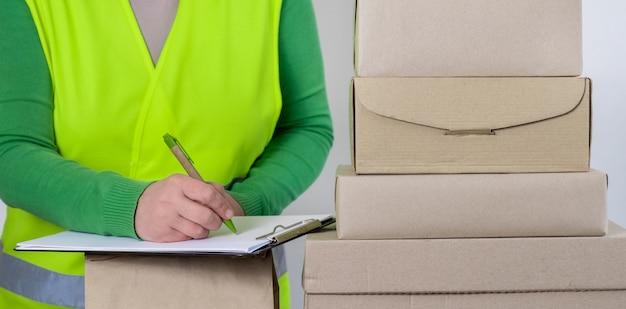 空白の注文、配達の概念を持つ多くの紙箱の近くに立っている緑のベストの女性労働者。