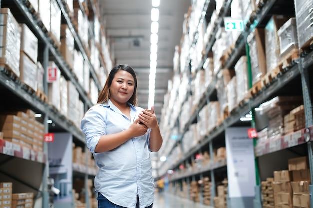 Работница проверяет коробку с продуктами во время работы на большом складе