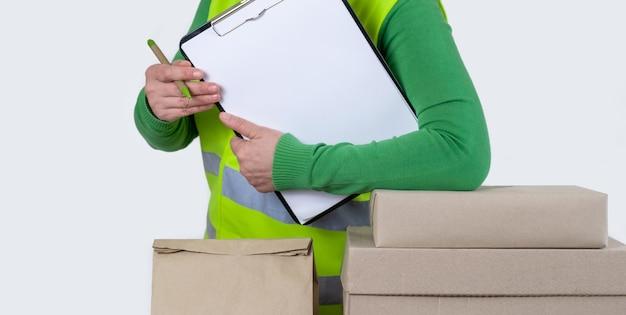 Работница в зеленом жилете стоит возле множества бумажных коробок с пустым заказом, концепция доставки.