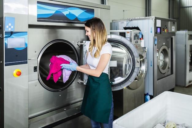여성 노동자가 세탁소에서 세탁물을 세탁기에 싣고 있습니다.