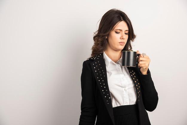 Lavoratrice che guarda la tazza con un'espressione illeggibile