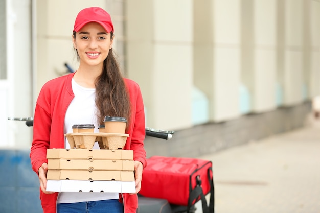 야외 스쿠터 근처 음식 배달 서비스의 여성 노동자