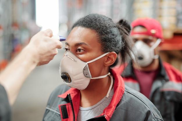 背後にいる他の労働者と一緒に体温を測定している呼吸器と作業服の大きな倉庫または工場の女性労働者
