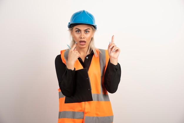 흰색 바탕에 거꾸로 가리키는 여성 노동자. 고품질 사진