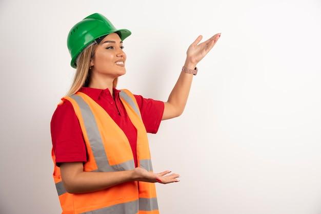 Работница позирует в шлеме и униформе.