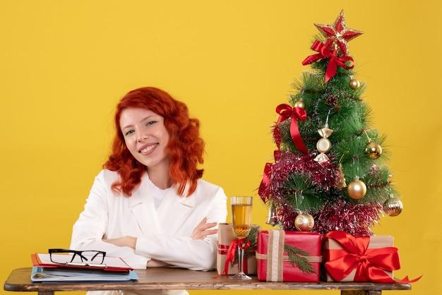 Работница сидит за своим столом с маленькой елкой и подарками на желтом