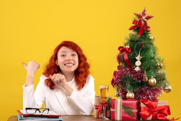 黄色のプレゼントやファイルとテーブルの後ろに座っている女性労働者