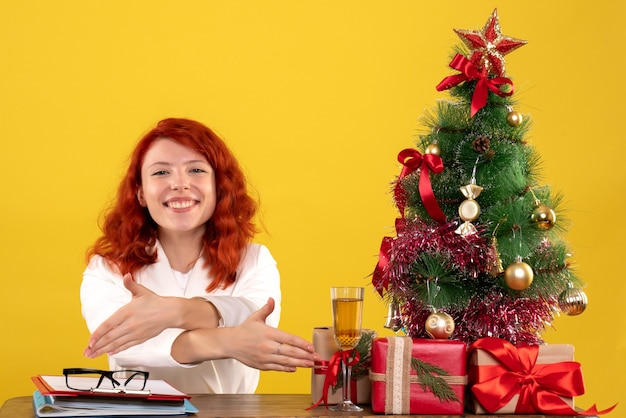 Female worker sitting behind table with christmas presents and tree on yellow floor office xmas new year color