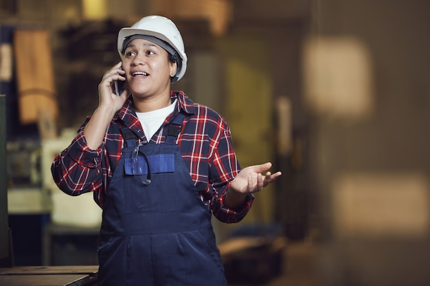 Female worker speaking by phone at plant