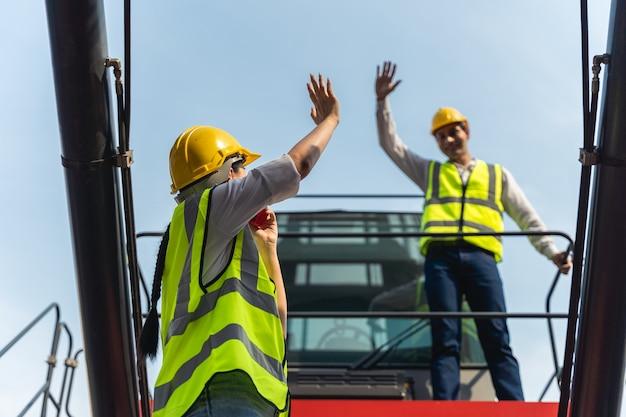 立って黄色いヘルメットをかぶった女性労働者が荷積みを管理し、貨物貨物船からのコンテナの品質をチェックして、輸出入を出荷します