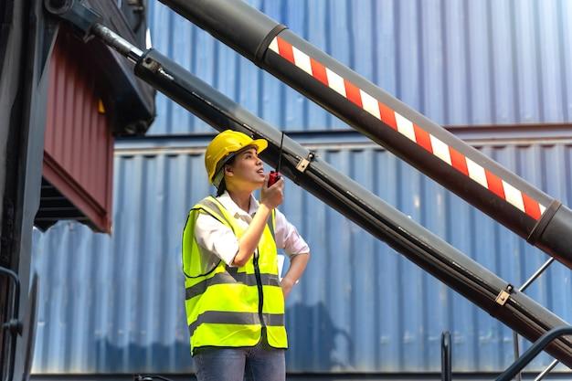 Работница, стоящая и одетая в желтый шлем, контролирует загрузку и проверяет качество контейнеров с грузового грузового судна для доставки импорта и экспорта