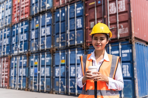 Female worker standing and wear a yellow helmet control loading and check a quality of containers from cargo freight ship for shipping import and export