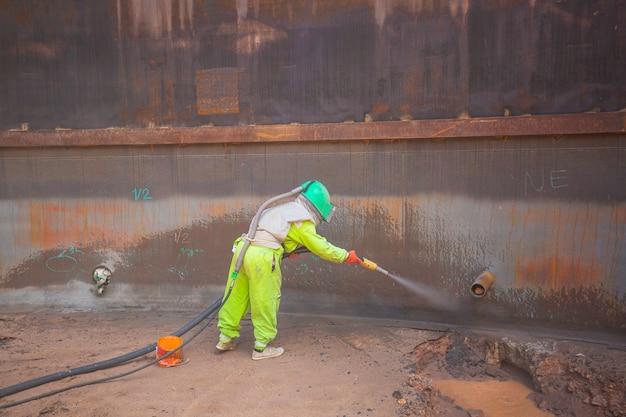タンク内部油のサンドブラストによる女性労働者表面腐食板の準備