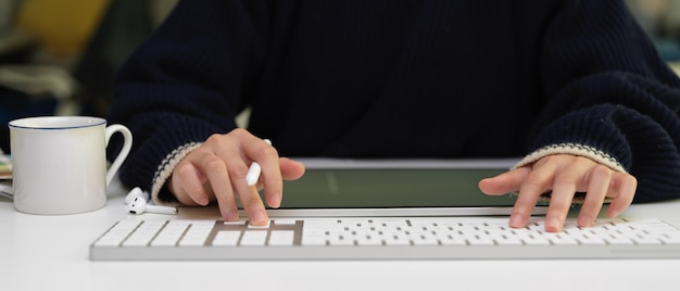 Female worker typing on computer keyboard on white office desk with wireless earphone, digital tablet and office supplies