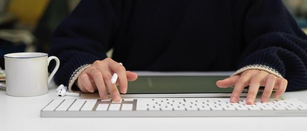 무선 이어폰, 디지털 태블릿 및 사무 용품 흰색 사무실 책상에 컴퓨터 키보드에 입력하는 여성 노동자
