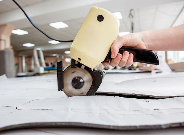 女性労働者は、電気切断機を使用しています。ファブリック業界の生産ライン。