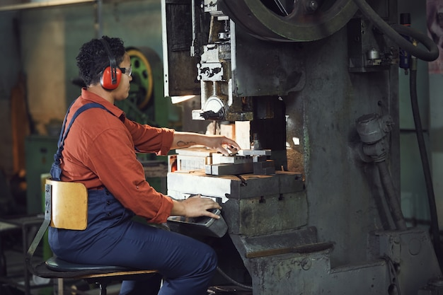 Female worker using heavy machine at plant