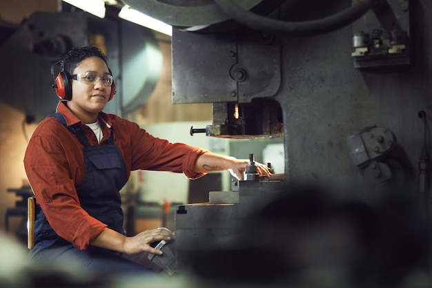 Female worker using heavy machinery at factory