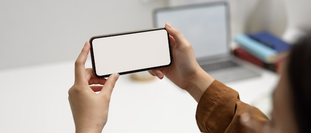 Female worker using horizontal mock-up smartphone in office room with laptop and supplies in blurred background