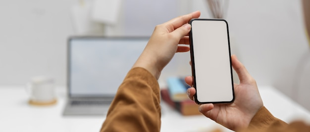Female worker using mock-up smartphone in office room with laptop and supplies in blurred background