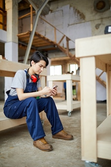 Female worker using smartphone at break