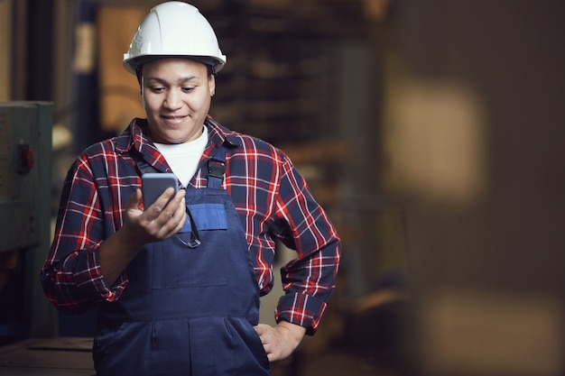 Female worker using smartphone at plant