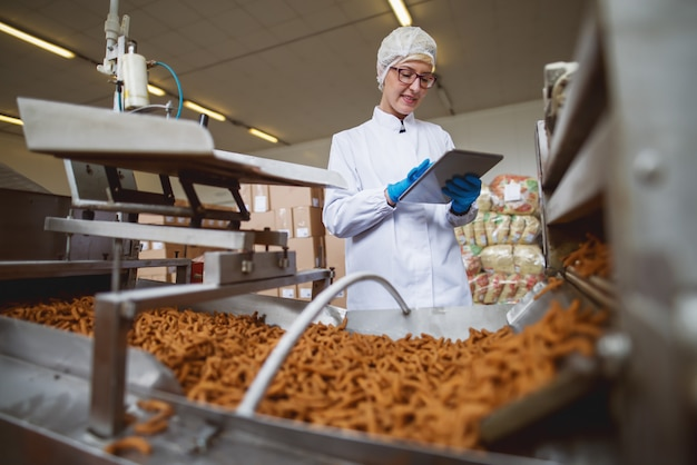 식품 공장에 서있는 동안 제품을 제어하기 위해 태블릿을 사용하는 여성 노동자.