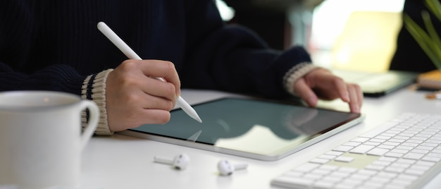 무선 이어폰, 컴퓨터 장치 및 사무 용품 흰색 사무실 책상에 스타일러스와 태블릿을 사용하는 여성 노동자