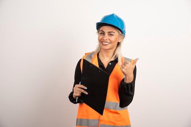 白い背景に親指を立てるクリップボードを持つ女性労働者。高品質の写真