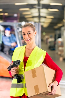 Female worker with protective vest and scanner, holds package, standing at warehouse of freight forwarding company,