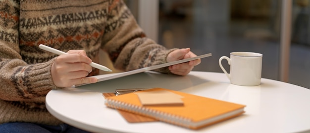 Female worker working from home with digital tablet and schedule books on coffee table