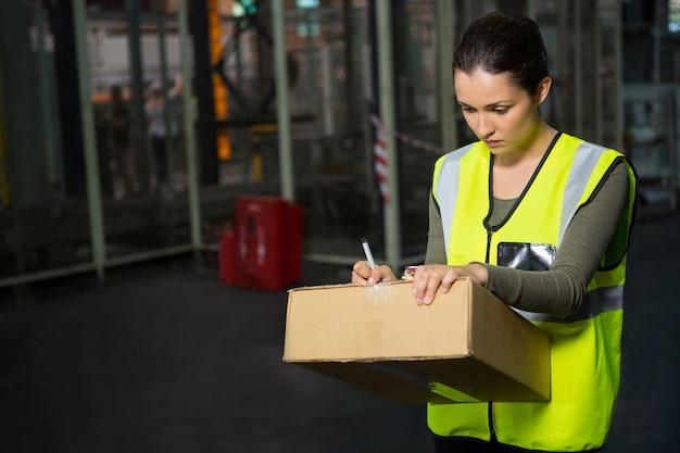 Lavoratore di sesso femminile che scrive sulla scatola in magazzino