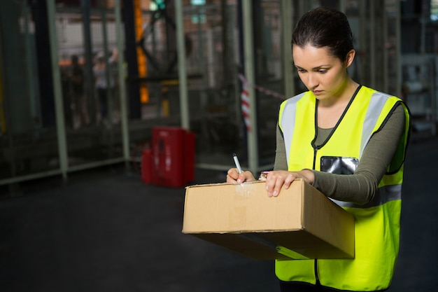 Female worker writing on box in warehouse