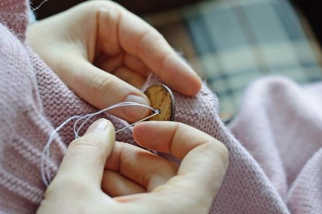 女性労働者の手が木製のボタンをジャケットに縫い付けています。閉じる。