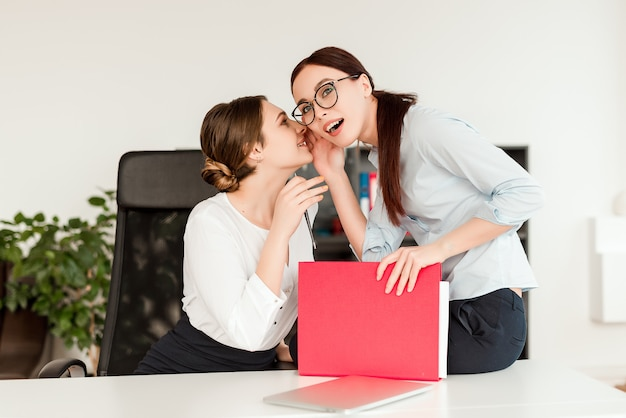 Female workers share secret at work and whispering news to each other
