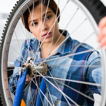 Female working at bike wheel