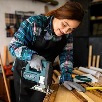 ハンマードリルでワークショップで働く女性