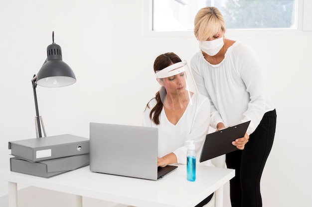 Female working in an office and wearing face protection front view