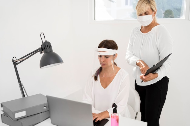 Female working in an office and wearing face protection