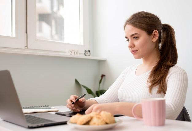 Женщина работает на ноутбуке дома стол